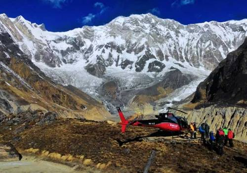 Red helicopter and travellers at Annapurna Base Camp