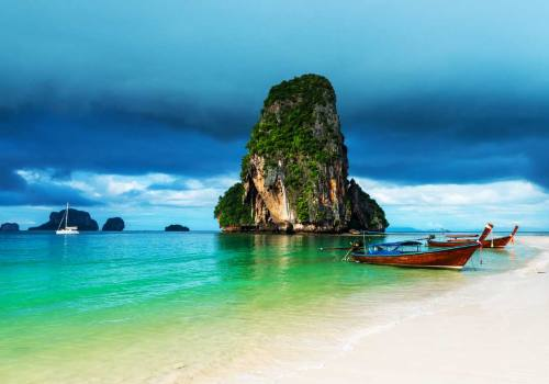 Wooden boats and high cliff in the sea in Phra Nang beach, Krabi Thailand